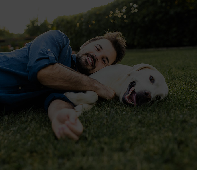 a man laying on the lawn with his dog